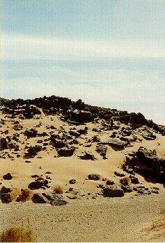 Die schwarzen Steine auf dem hellen Sand sehen in der Sonne eindrucksvoll aus